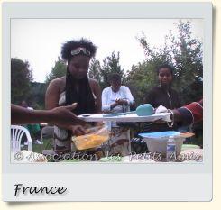 Le 16 août 2008 en après-midi, une membre bénévole de l'APA et d'autres participants au barbecue de Villetaneuse (93), en France. [Photographie © Association les Petits Amis.]